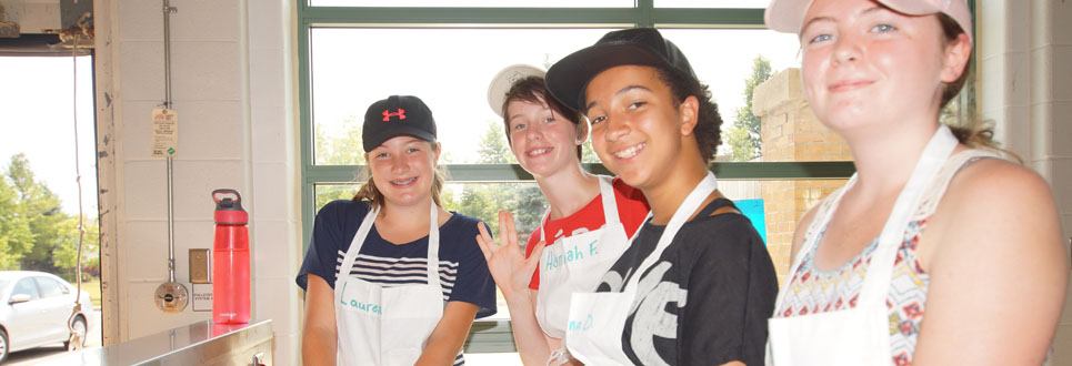 Four female students in a kitchen cooking and wearing hats and white aprons