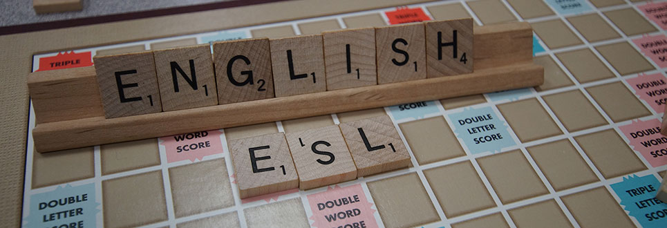 "Scrabble board with ""ENGLISH"" and ""ESL"" laid out with the letter pieces."